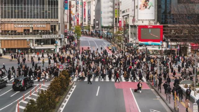 歩行者や車群集の4k 時間経過は、未定義の人が道路の交差点を歩いている渋谷区東京市にある交差ウォーク。日本文化・商店街構想 - 地下鉄駅点の映像素材/bロール