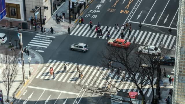 4k zeitraffer von fußgängern drängen undefinierte menschen, die den straßenabschnitt überqueren, der in ginza tokio, japan, zu fuß geht. japanische kultur und gehobenes einkaufsgebietskonzept - zeitraffer fast motion stock-videos und b-roll-filmmaterial