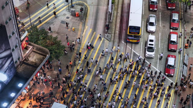 tl/ time lapse of people and commuters crossing pedestrian crossing in central hong kong, aerial view - öffentliches verkehrsmittel stock-videos und b-roll-filmmaterial