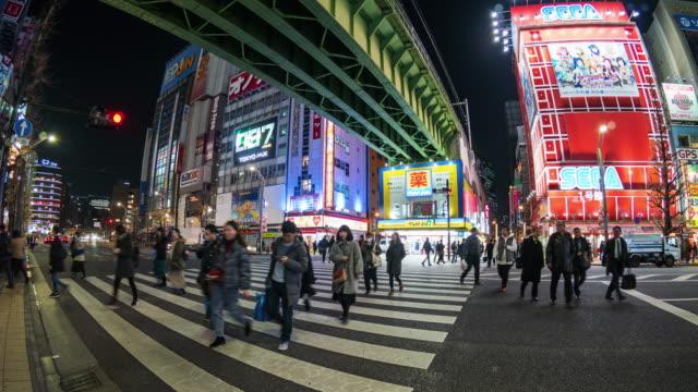 4K Zeitraffer von Menschen drängen sich, die die Straßenkreuzung mit dem Autoverkehr in Akihabara in der Nacht, Tokio, Japan, überqueren. Konzept für japanische Kultur-und Elektrostadt-Shopping-Bereiche
