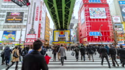 4K Time lapse of people crowd walking overpass the street intersection cross-walk with car traffic in Akihabara Tokyo city, Japan. Japanese culture and electric town shopping area concept