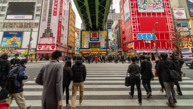 4k time lapse of people crowd walking overpass the street intersection cross-walk with car traffic in akihabara tokyo city - akihabara station stock videos and b-roll footage