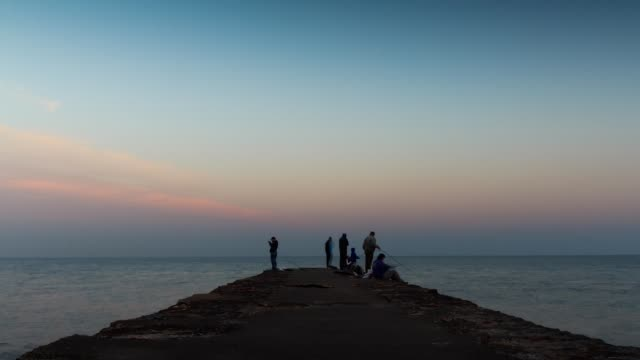 time lapse of people fishing at sunset in montevideo, uruguay - zeitraffer tag bis dämmerung stock-videos und b-roll-filmmaterial