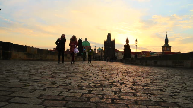time lapse of people walking over the charles bridge in prague, crossing the moldava river on early morning during sunrise in a new day in the city. - old town bridge tower stock videos and b-roll footage