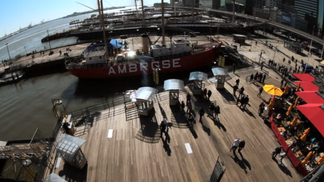 time lapse of people wandering around a pier with boats docked - lightship stock videos & royalty-free footage