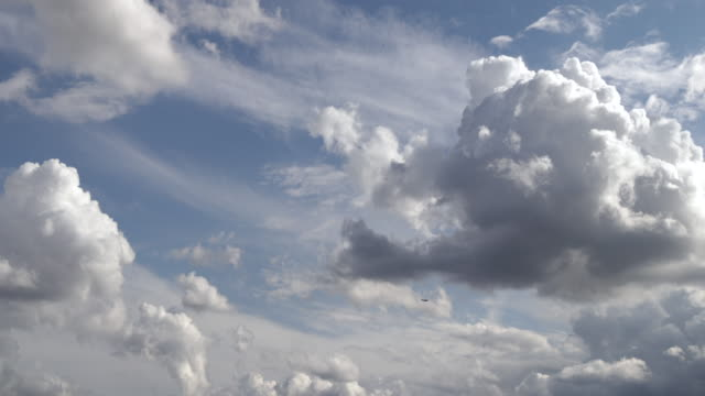 vídeos de stock, filmes e b-roll de time lapse of planes flying against white clouds billowing in a blue sky - vento