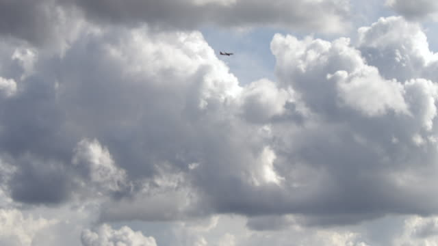 Time lapse of planes flying against white clouds billowing in a blue sky