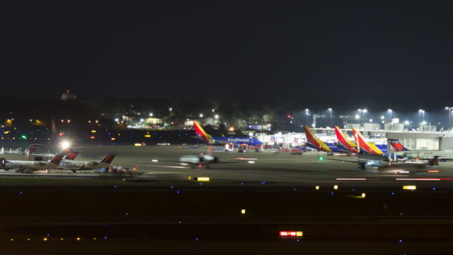 time lapse of planes taxiing and taking off  from the atlanta international airport at night - beengt stock-videos und b-roll-filmmaterial