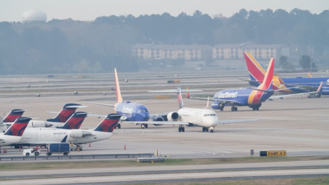 time lapse of planes taxiing and taking off from the atlanta international airport - start und landebahn stock-videos und b-roll-filmmaterial