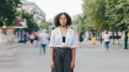 Time lapse of pretty Afro-American student standing in urban street outdoors