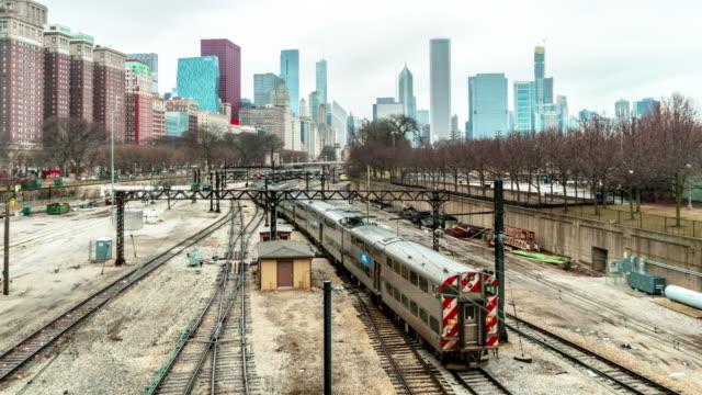 vídeos de stock, filmes e b-roll de lapso de tempo 4k de trilhas da estrada de ferro com trens entre o edifício moderno em chicago, illinois, eua - metrô de chicago