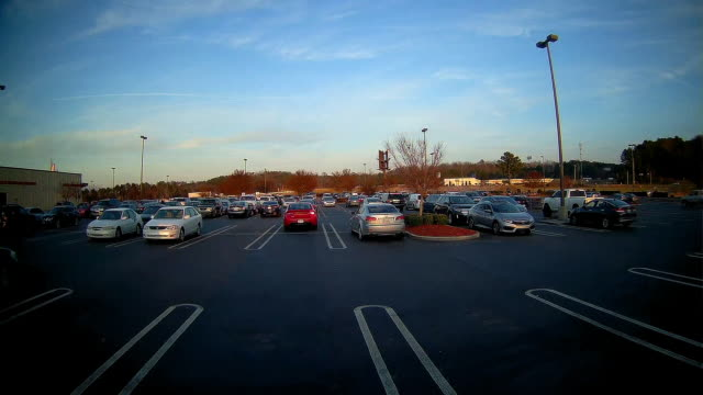 time lapse of rear dash cam shot of parking lot and highway traffic in the background. - car park stock videos & royalty-free footage