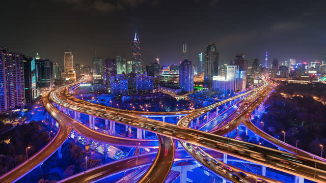 tl/ time lapse of road intersection with neon lighting, busy with rush hour commuter traffic, elevated view - purple stock videos & royalty-free footage