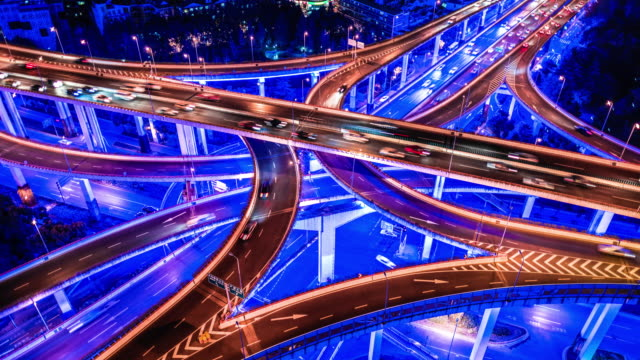 time lapse of road intersection with neon lights, aerial view