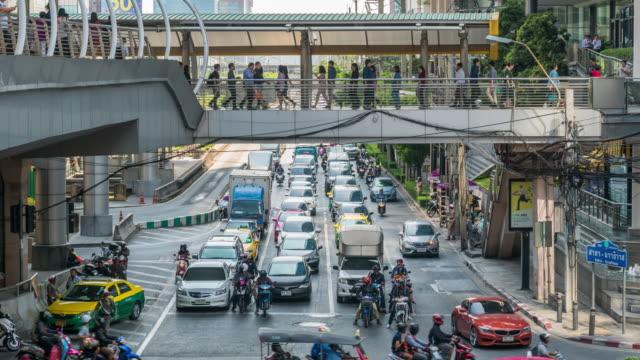vidéos et rushes de laps de temps de 4k de route avec un trafic jam et bondé de passants anonymes sur viaduc en heure de pointe au bts chong nonsi bangkok, de transport et le passager voyagent concept - circulation routière