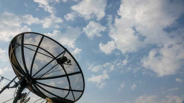 4K : Time lapse of satellite dish with clouds in blue sky background