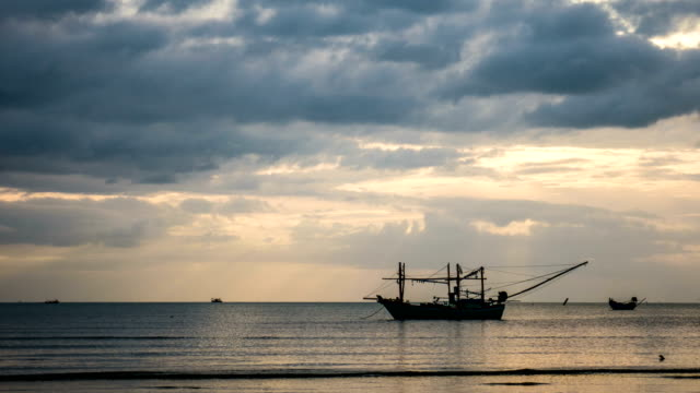 Time lapse of Sea and Silhouette Fishing Boat with Dramatic Sky in the Morning