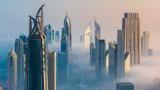 vídeos de stock, filmes e b-roll de time lapse of sheikh zayed covered in a sea of fog at dawn - futurista