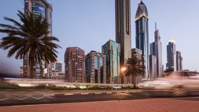 vidéos et rushes de tl/ time lapse of sheikh zayed road and dubai skyline, busy with commuting traffic at dusk, situated in dubai's financial district - low angle view