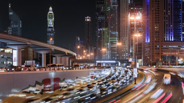 tl/ time lapse of sheikh zayed road , busy with commuting traffic at night, situated in dubai's financial district - light trail stock videos & royalty-free footage