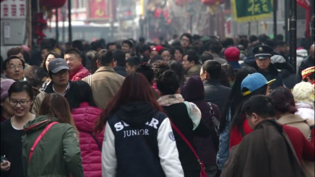 time lapse of shoppers and pedestrians walking through the qianmen area of beijing china on saturday march 14 2015 - military recruit stock videos and b-roll footage