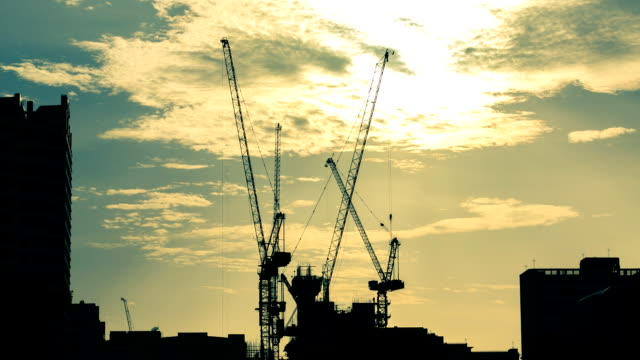 time lapse of silhouettes construction cranes against the evening sky. - crane stock videos & royalty-free footage