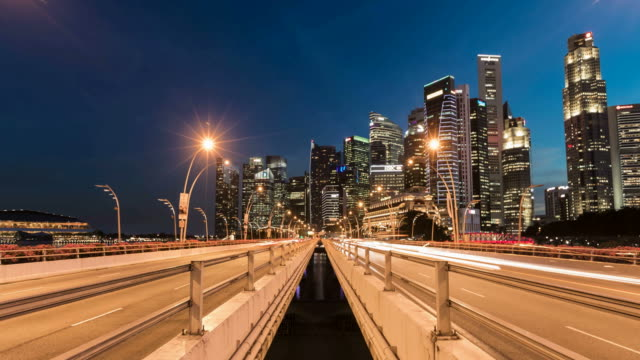 Time lapse of Singapore business center at night with traffic
