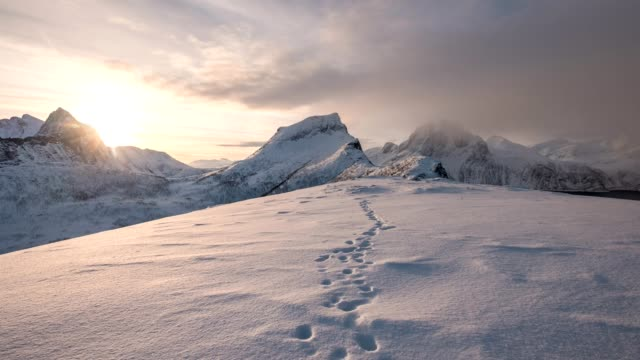 time lapse of snowy mountain range with footprint on snow at sunrise morning - track imprint stock videos and b-roll footage