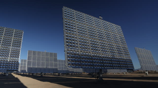 vídeos de stock e filmes b-roll de time lapse of solar panels on solar farm moving as they track the movement of the sun on a sunny day - painel solar