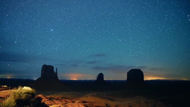 time lapse of stars and shooting stars in the night sky with silhouettes of rock formations in the distance in the monument valley desert in utah/arizona at night - dramatic landscape stock videos & royalty-free footage