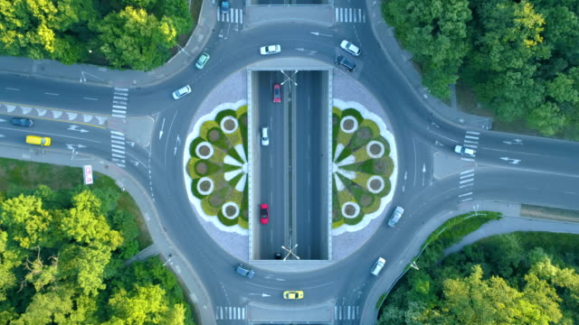 time lapse of stationary drone aerial view looking down on traffic circle in the city - roundabout stock videos & royalty-free footage