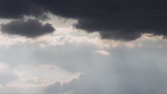 stockvideo's en b-roll-footage met time lapse of sun rays as dark grey clouds roll in overhead - grijs