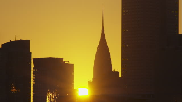 time lapse of sun rising behind top of chrysler building in new york city - chrysler building stock videos and b-roll footage