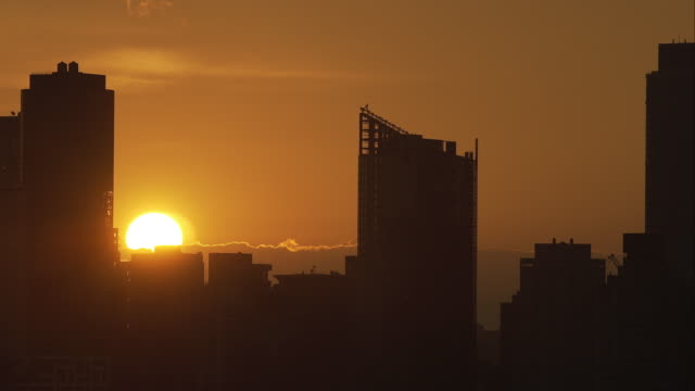 time lapse of sun rising over manhattan skyline - film montage stock videos & royalty-free footage
