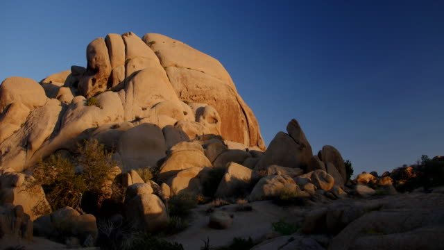 time lapse of sun setting on rocks, joshua tree national park - 巨礫点の映像素材/bロール