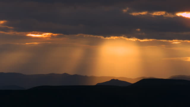 Time lapse of sunburst and rays of sunlight through stormy sky over New Mexico plateau