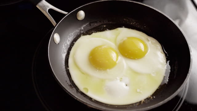 time lapse of sunny side eggs frying in a skillet on a stove in a kitchen - fried stock videos & royalty-free footage