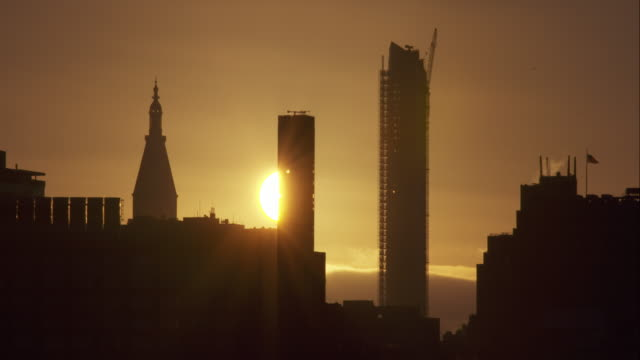time lapse of sunrise behind tall new york city skyscrapers including one under construction - 修理する点の映像素材/bロール