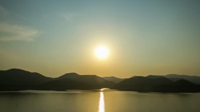 vídeos de stock, filmes e b-roll de lapso de tempo 4k do por do sol atrás da montanha na província tailândia de chiang mai - dam