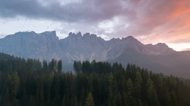 Time Lapse of sunset sky and cloudy in carezza lake and pine tree , dolomites south tyrol Italy