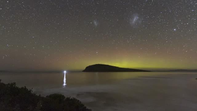 vídeos de stock, filmes e b-roll de time lapse of the aurora australis or southern lights behind an island in the ocean, tasmania - espaço e astronomia