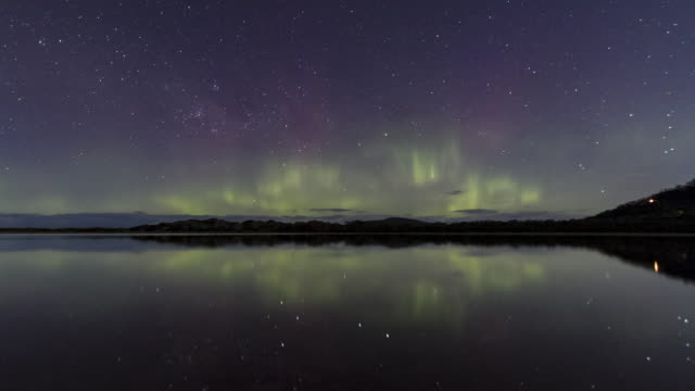 time lapse of the aurora australis or southern lights from tasmania, reflected in still water. - aurora australis stock videos & royalty-free footage