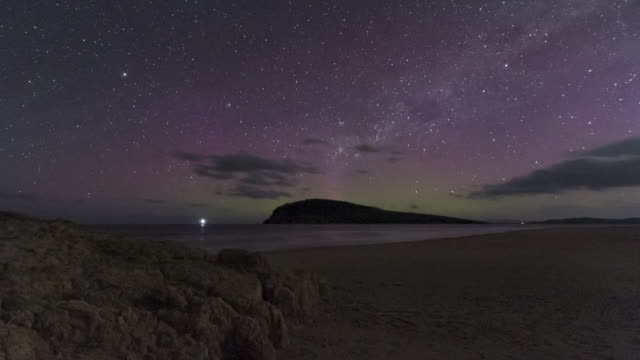 time lapse of the aurora australis or southern lights on a beach in tasmania with a lone figure in silhouette looking on. - aurora australis stock videos & royalty-free footage