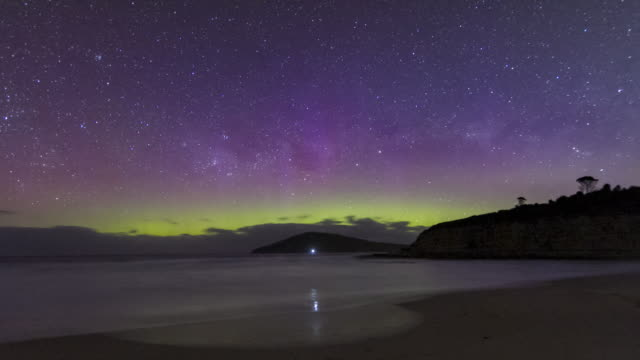 time lapse of the aurora australis or southern lights over a beach in tasmania, with a lone figure watching on. picket fence formation and colourful aurora. - aurora australis stock videos & royalty-free footage