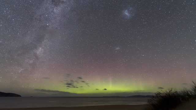 time lapse of the aurora australis or southern lights over a beach in tasmania, featuring a green blob formation. - aurora australis stock videos & royalty-free footage