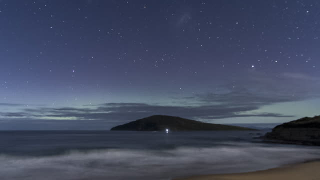 time lapse of the aurora australis or southern lights over an island in the ocean, from moonlit to darkness - aurora australis stock videos & royalty-free footage