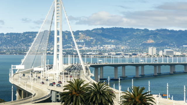 time lapse of the bay bridge bridge traffic - baia di san francisco video stock e b–roll