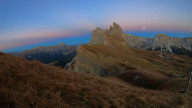 Time lapse of the beautiful Dolomites mountains on the top of the Seceda mountains at dusk. 4K.