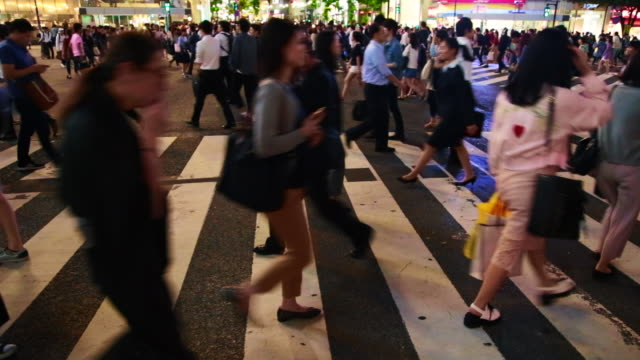 Time lapse of the bustling pedestrian crossing in Shibuya with people and cars during work day at night.