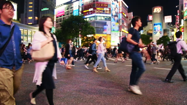 time lapse of the bustling pedestrian crossing in shibuya with people and cars during work day at night. - pedestrian stock videos and b-roll footage